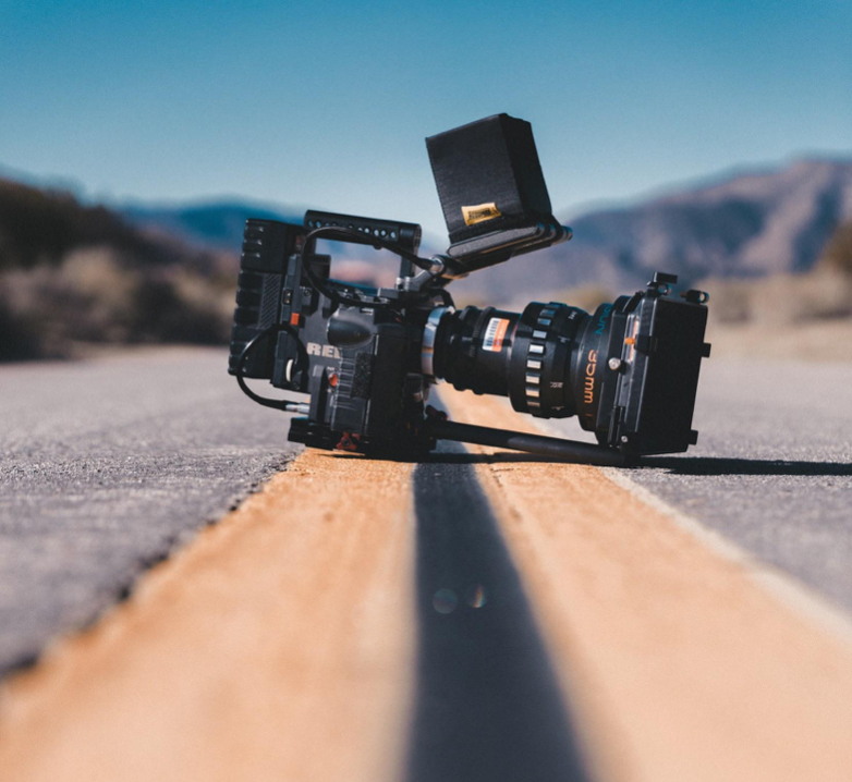 a film camera sits in the middle of a road