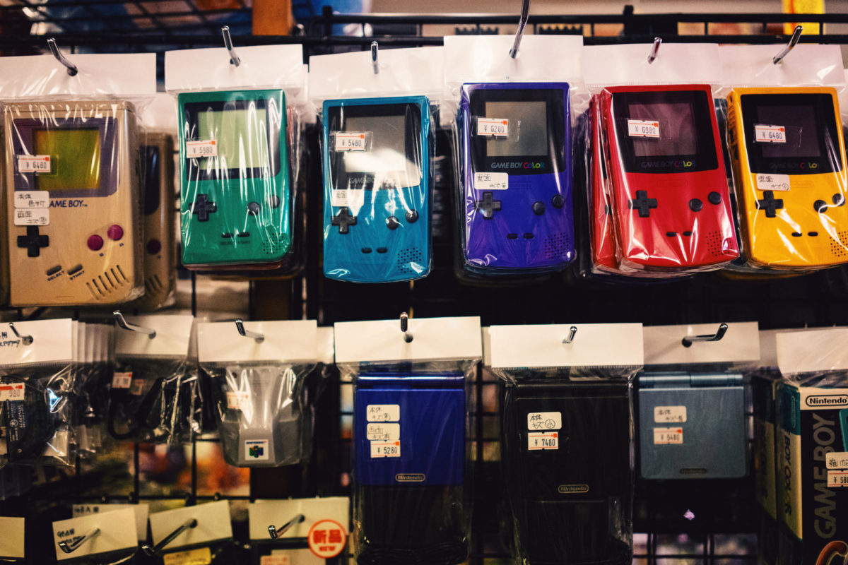 backpacks in the shape of gameboys. Colors include navy, forest green, gray, mustard yellow, and red